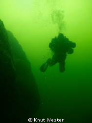 a diver svimming next to wall at the swedish island gotland. by Knut Wester 
